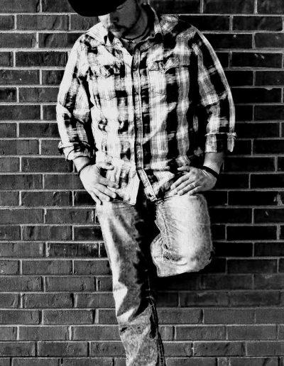 Country artist Jamie Brabham leaning on brick wall.